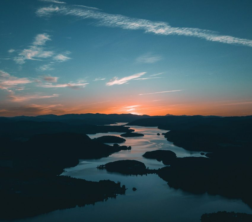 aerial-photography-of-water-beside-forest-during-golden-hour-1144176